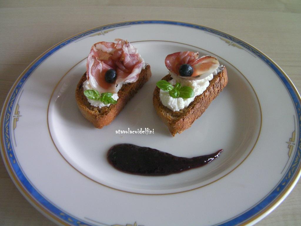 Crostini di semola rimacinata al Primitivo con ricotta asquant, capocollo, germogli di basilico e crema di Primitivo agli agrumi