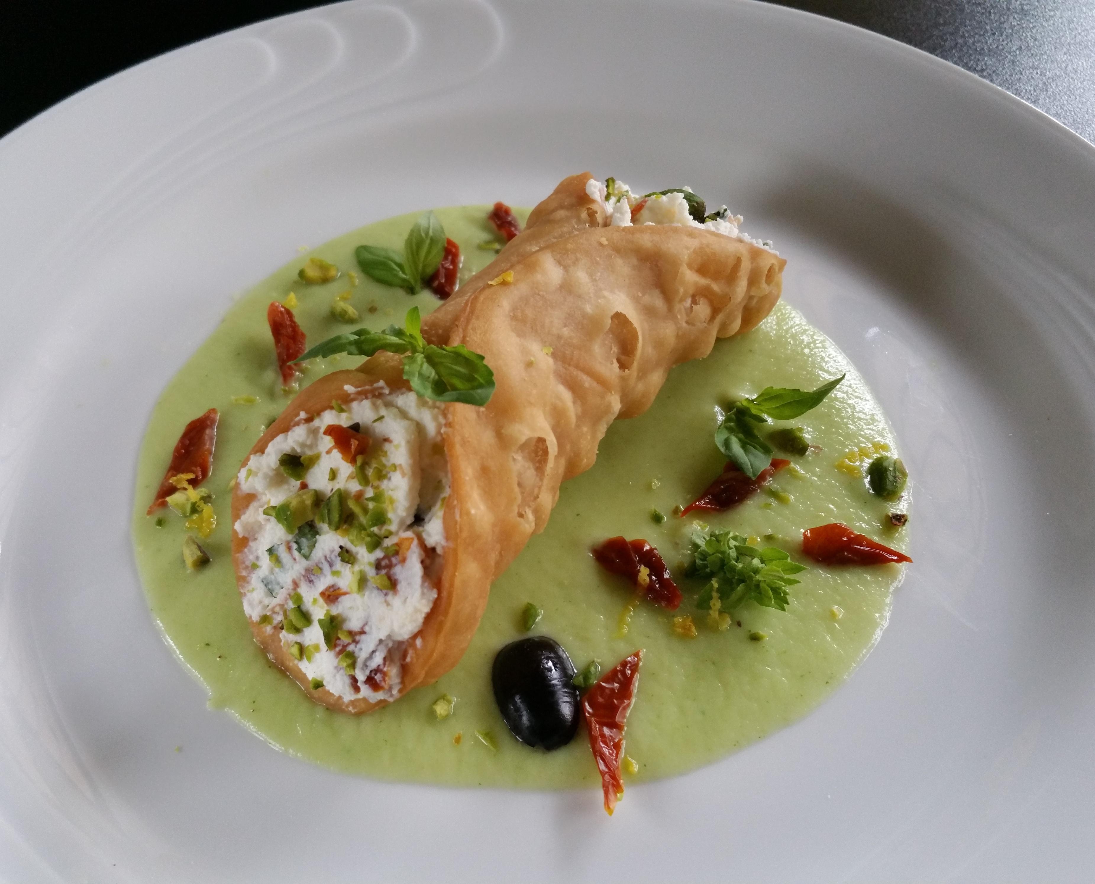 Cannolo salato con ricotta, pomodori secchi, olive leccino e pistacchi su crema di broccoli romani