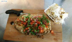 Pinsa con mozzarella, prosciutto, pomodori e rucola